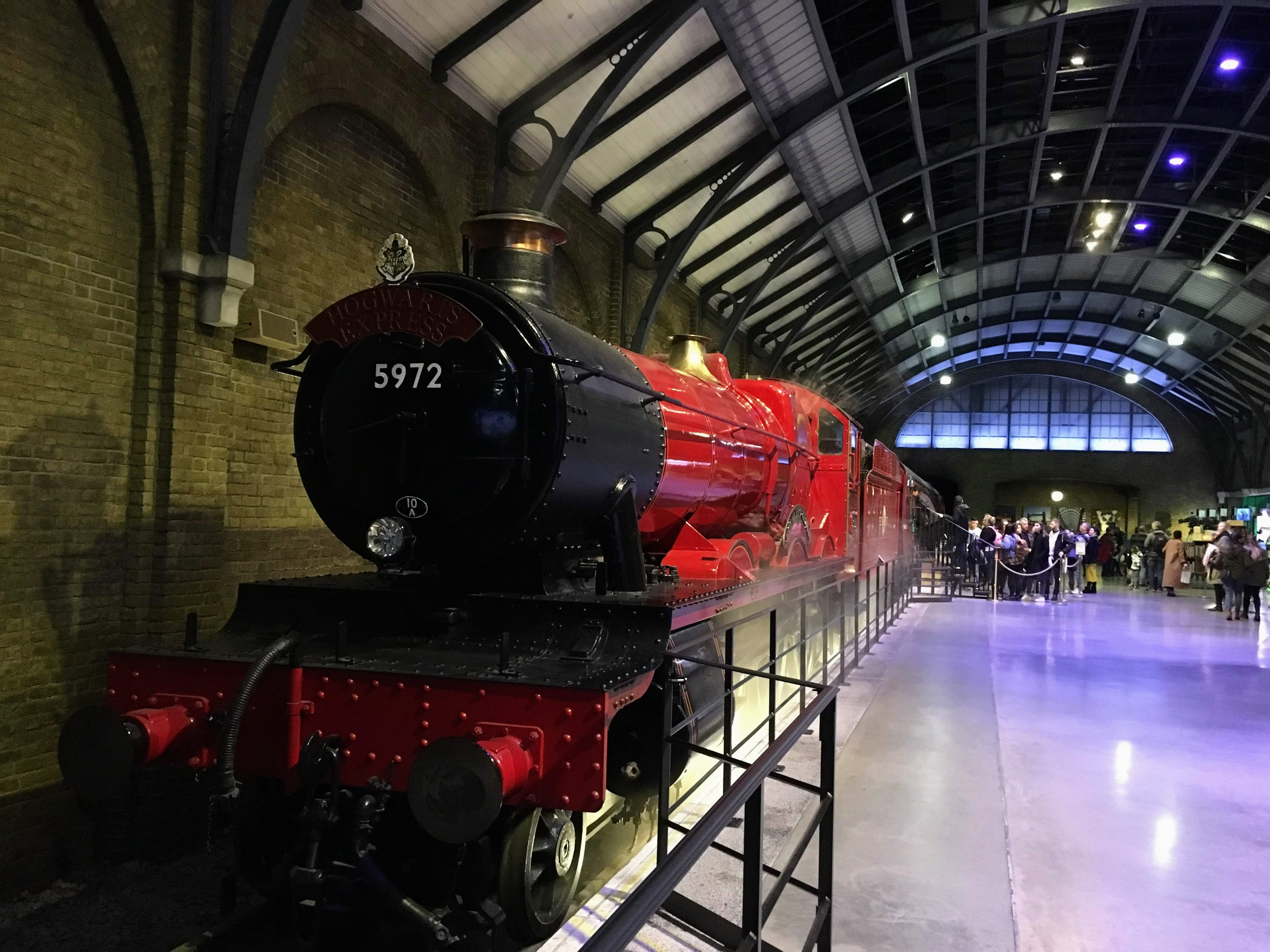 People waiting in line to enter the Hogwarts Express movie prop inside the Harry Potter Studios London Warner Bros