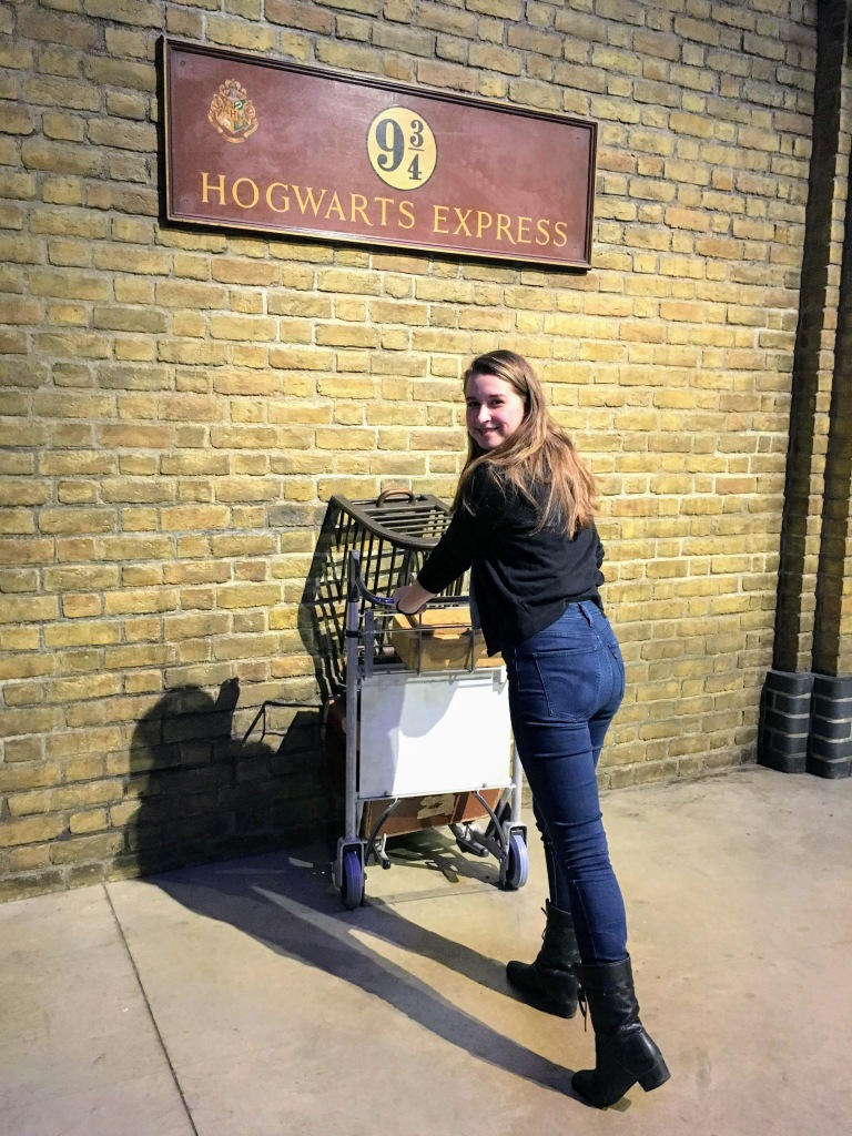girl pushing a trolley through the wall at the Harry Potter Studios Tour Platform 9 3/4 Warner Bros London