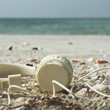 Travel Podcasts hosted by women headphones beach