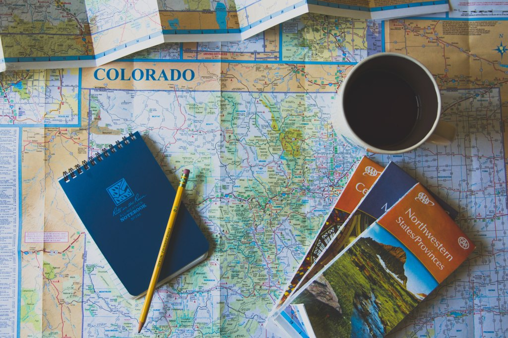 map of Colorado travel guides cup of coffee notebook plan a solo city trip travel destination