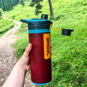 hand holding a Grayl Geopress water filter bottle background a hill with forest and hiking trail