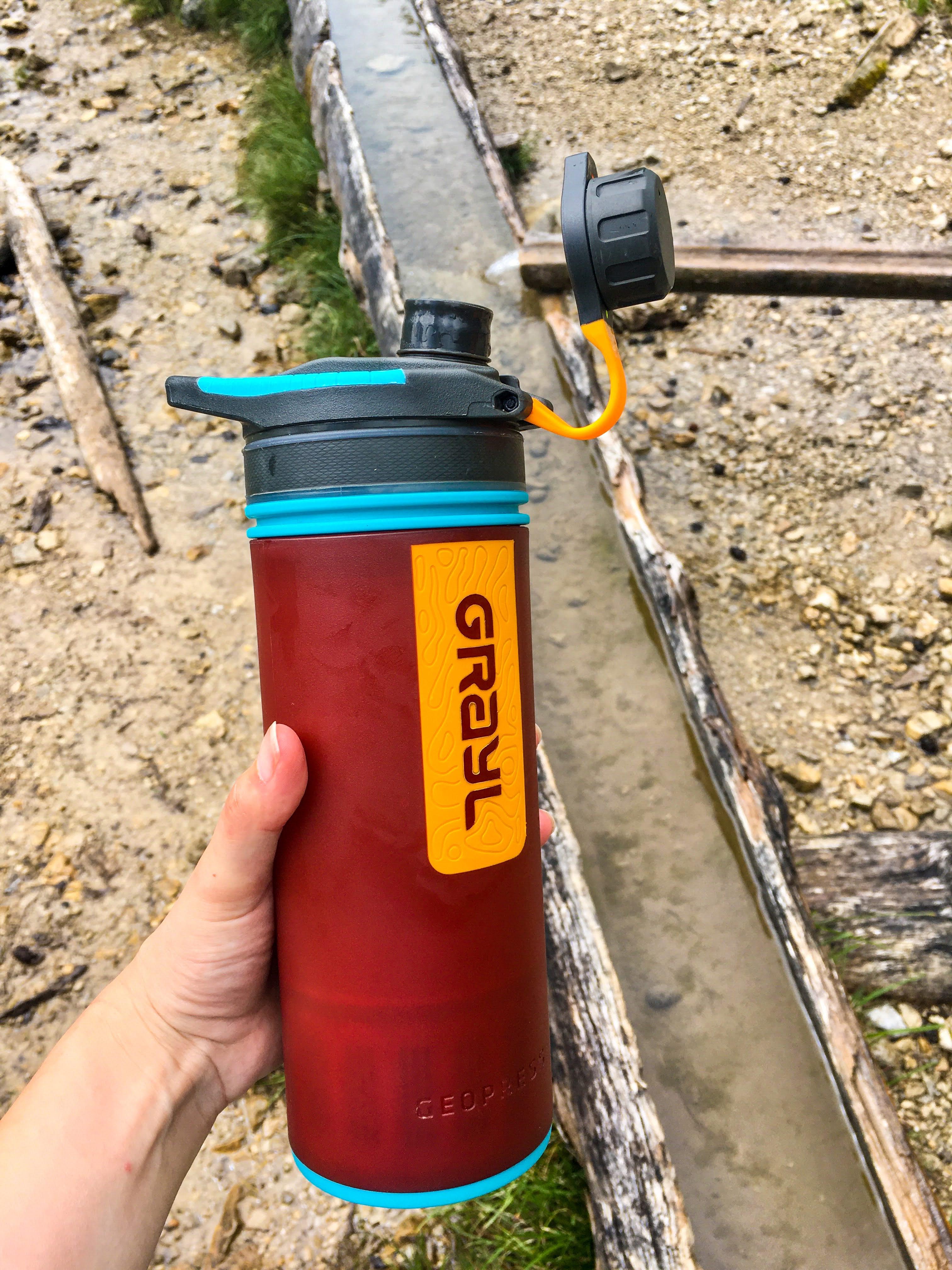 hand holding a Grayl Geopress wter filter bottle